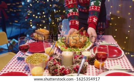 Christmas dinner. Picture showing man in sweater placing roast hot turkey preparing dining table with meals. Family celebration. Winter holidays.