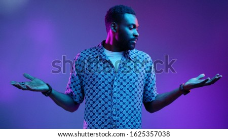 Young Afro American attractive man with widely opened eyes having hesitation shrugging his shoulders expressing uncertainty. Facial expressions, life perception and attitude concept. Male portrait #1625357038