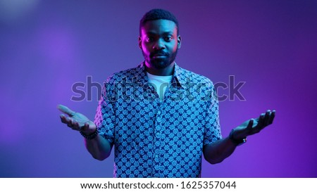Young Afro American attractive man with widely opened eyes having hesitation shrugging his shoulders expressing uncertainty. Facial expressions, life perception and attitude concept. Male portrait #1625357044