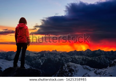 Adventurous Girl watching the Beautiful Dramatic Sunset on top of the Mountains. Composite Image with Landscape taken in British Columbia, Canada. Concept: Adventure, Hike, Outdoors, Sport,  #1625358985
