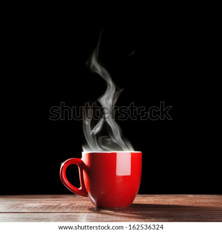 Steaming coffee cup on dark background Royalty-Free Stock Photo #162536324