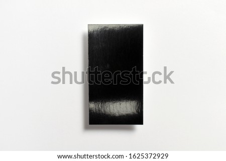 Black blank glossy textured business card flying and isolated on white background, us standard size 3.5 x 2 inches, real professional studio photo.  Royalty-Free Stock Photo #1625372929