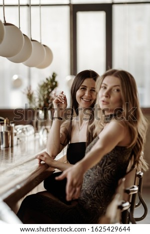 Two gorgeous young women sitting at the bar, day time. Blond and dark long hair girlfriends hanging out. Celebration, party, glamourous dressed #1625429644