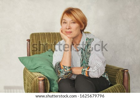 Nice mature woman with short ginger hair sitting on green armchair at home #1625679796