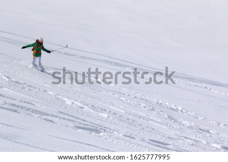 Snowboarder downhill on snowy off piste slope with newly-fallen snow at high winter mountains #1625777995