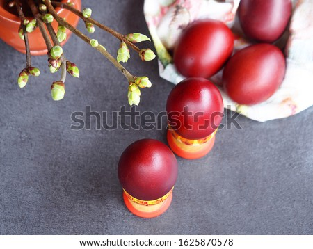 Natural Easter eggs in wooden stands and twigs with young lilac leaves on a gray background closeup. Spring bright picture with painted eggs and greenery for the Easter holiday top view.