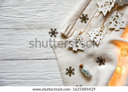 Christmas decorations on a white wooden background. White woolen hat and scarf, white wooden fir trees on a lace, silver snowflakes, decorative lighting and decorative bottle with sparkles. #1625884429