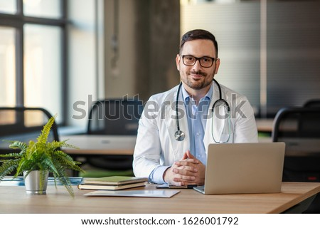 Doctor man sitting at the desk at his working place and smiling at camera. Perfect medical service in clinic. Portrait of a handsome young doctor. Happy doctor looking at camera  #1626001792