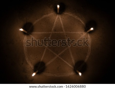 White pentagram symbol on concrete ground. Illuminated with candles. Dark background. Scary, mystical occultism  #1626006880