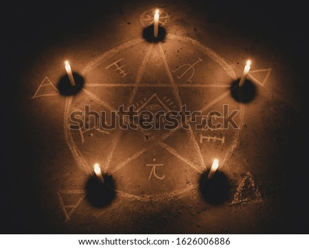 White pentagram symbol on concrete ground. Illuminated with candles. Dark background. Scary, mystical occultism  #1626006886