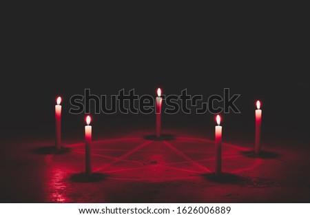White pentagram symbol on concrete ground. Illuminated with candles. Dark background. Scary, mystical occultism  #1626006889