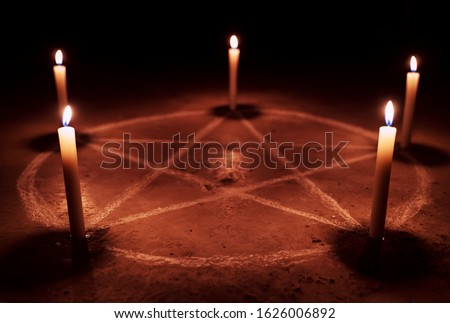 White pentagram symbol on concrete ground. Illuminated with candles. Dark background. Scary, mystical occultism  #1626006892