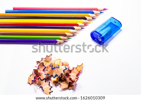 Multi-colored, bright sharpened pencils in different positions on a white background. Pencil sharpener. Pencil shavings. #1626010309