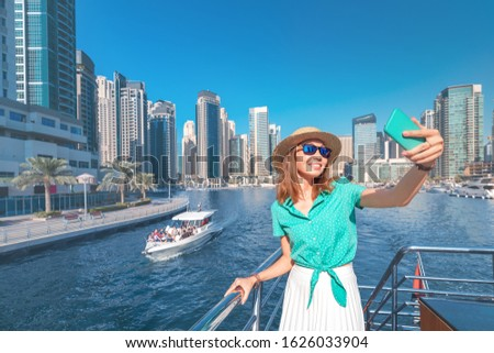 Happy girl traveler taking selfie photo for her social networks in modern Finance center and bay area. Student and Tourist Blogger lifestyle concept