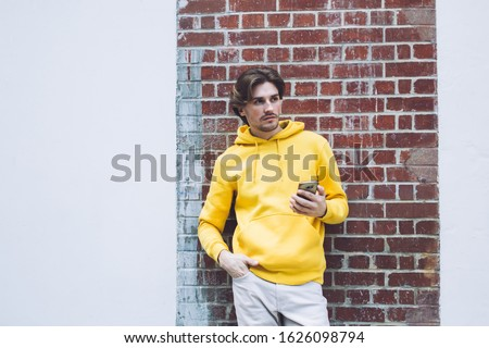 Pensive casually dressed young man in yellow sweatshirt standing back to brick wall with one hand in pocket while holding phone in other hand #1626098794