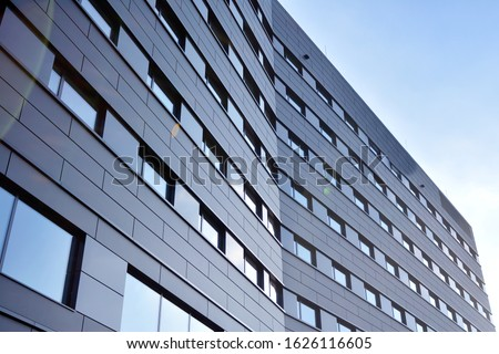 A view at a straight facade of a modern building with a dark grey facade. Dark grey metallic panel facad. Modern architectural details.  Royalty-Free Stock Photo #1626116605