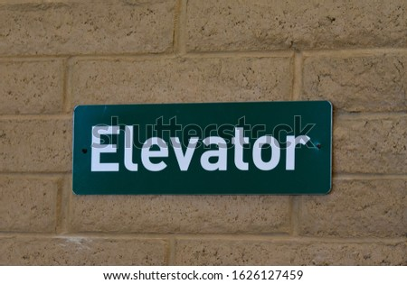 Green Elevator Sign On Brick Wall