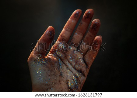 Female hand covered with sequins. The movement of the palm of your hand and Shine multicolored glitter, mystical and abstract mood. Defocused light #1626131797