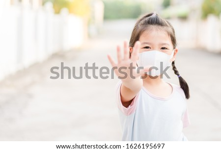 Coronavirus Covid-19.Stay at home Stay safe concept.Little chinese girl wearing mask for protect.show stop hands gesture for stop corona virus outbreak.Coronavirus pandemic virus symptoms.Home school. #1626195697