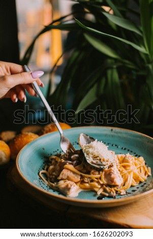 A girl eating a chicken fillet and macarooni #1626202093
