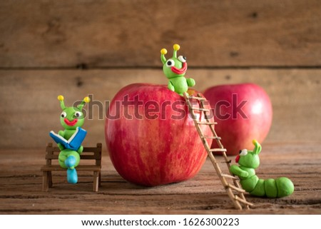 Green worms are made of plasticine and apple.Cartoon style worm.House of worms in apples