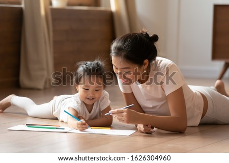 Smiling Vietnamese young mom and little biracial daughter lie on warm wooden heated floor in living room drawing painting together, happy ethnic mother or nanny relax play with small Asian girl child