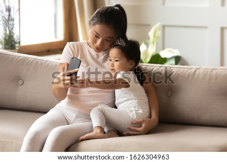 Vietnamese millennial mom and little biracial daughter sit on couch make self-portrait picture on smartphone together, happy Asian mother nanny play with small ethnic girl child take selfie on cell