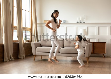 Overjoyed young Asian mom and cute little biracial daughter have fun dancing in living room together, happy millennial mother play involved in funny activity with small Vietnamese girl child at home #1626304984