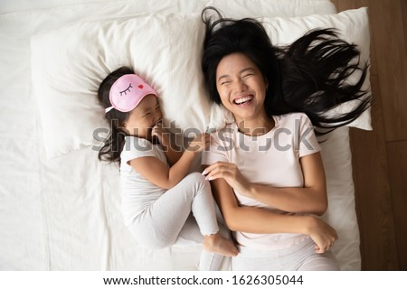 Top view of overjoyed young Asian mother lie in comfortable bed with small biracial girl child have fun in bedroom together, happy Vietnamese mom and little daughter laugh enjoy early morning at home #1626305044
