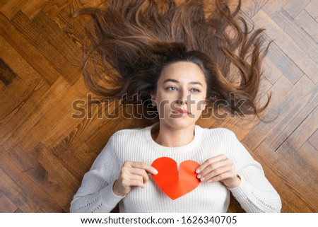 Unhappy young woman with broken heart tearing up a red paper heart. Lying on the ground, unhappy and sad. Loneliness and divorce  #1626340705
