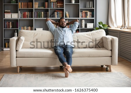 Serene relaxed barefoot young african man resting on comfortable couch in modern living room holding hands behind head, millennial hipster guy enjoy no stress peace of mind lounge on sofa at home #1626375400