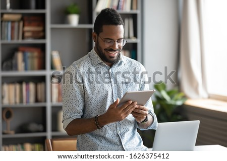 Smiling young african business man professional holding using digital tablet computer online app software on tech device modern pad gadget browse internet work communicate online stand at home office #1626375412