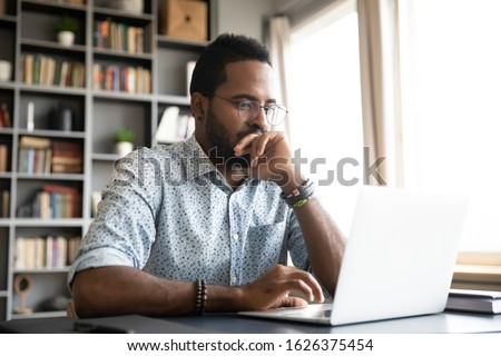 Focused concentrated young african businessman sit at desk look at laptop, serious afro american male professional analyst working online on computer data watch webinar thinking of problem solution #1626375454