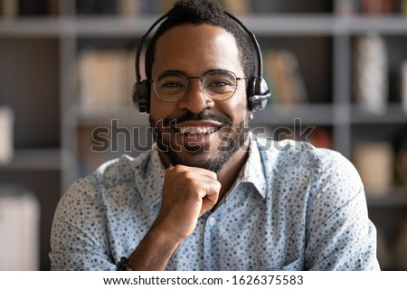 Smiling african professional telemarketer call center operator wear wireless headset look at camera, afro american business man customer technical customer support service closeup headshot portrait #1626375583