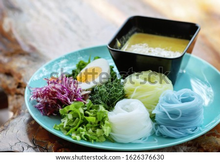 Thai Rice Noodle in traditional recipe with the curry dipping sauce on a table, selective focused picture of tasty Thai food called Khanomjeen in Thai language, tasty food in the restaurant, delicacy
