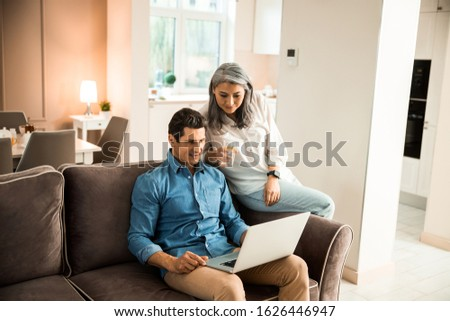 Smiling pretty mature wife sitting next to her husband in living room stock photo Royalty-Free Stock Photo #1626446947