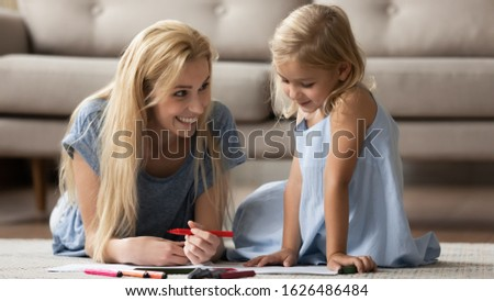 Adorable little child girl sitting on floor with smiling babysitter nanny, drawing pictures in paper album. Attractive young mother lying on carpet, teaching small daughter coloring pictures.