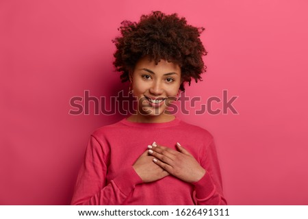 Portrait of touched lovely woman touches heart, makes sign of affection and gratitude, has gentle smile, wears crimson jumper, appreciates nice words, looks gratefully, isolated on pink wall #1626491311