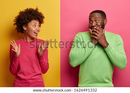 Surprised emotional Afro American woman tells funny story to boyfriend, raises palms, dark skinned guy giggles and covers mouth, hides emotions, wear colorful clothes, isolated over two colored wall #1626491332