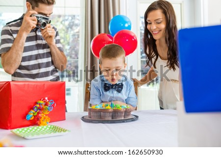 Father taking picture of son blowing out candles on cake at home