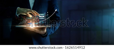 Businessman holding tablet and analysis stock market, currency exchange and banking, showing a growing virtual hologram of statistics, graph and chart, Business growth, planing and strategy  concept. Royalty-Free Stock Photo #1626514912