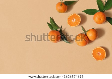 Styled stock photo. Decorative summer fruit composition. Whole and sliced orange tangerines, citrus fruit and leaves isolated on orange table background. Food pattern. Empty space. Flat lay, top view.