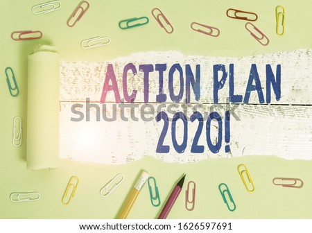 Handwriting text writing Action Plan 2020. Concept meaning proposed strategy or course of actions for current year Stationary and torn cardboard placed above a wooden classic table backdrop. #1626597691