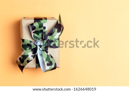 Gift box with khaki ribbon on the yellow background. Defender of the Fatherland Day, February 23. Space for text.
