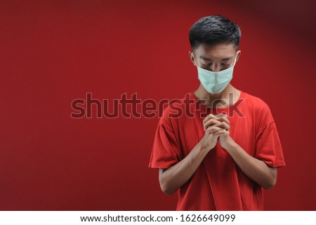 Portrait of  young Asian man wearing protective mask against the coronavirus, doing pray for corona virus is quickly overcome isolated on red color #1626649099