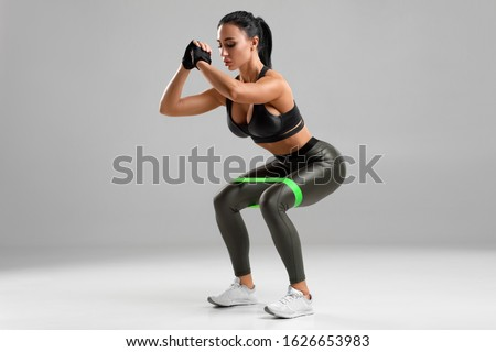 Fitness woman doing squats with resistance band on the gray background. Sporty girl squatting #1626653983
