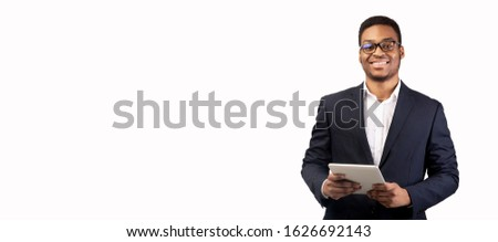 Salesman. Smiling black guy using tablet and looking at camera isolated over white studio wall, copyspace, panorama #1626692143
