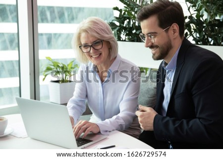 Happy middle aged female team leader working on computer with motivated young male colleague in eyeglasses. Professional smiling managers watching funny video, enjoying free break time at office. Royalty-Free Stock Photo #1626729574