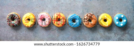 Various colourful donuts in a row on rustical grey background #1626734779