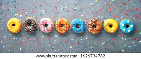 Various colourful donuts in a row with confetti on rustical grey background #1626734782